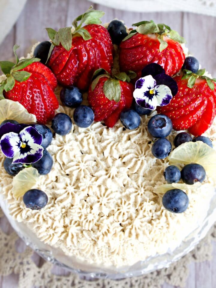 strwberry cake with cashew cream piping and berries on top.