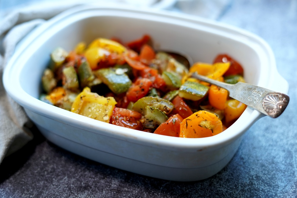 bell peppers, tomatoes and zucchini in oven pan.