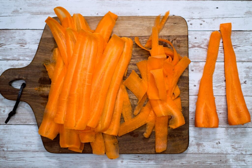 3 sizes of carrot peels on a cutting board..
