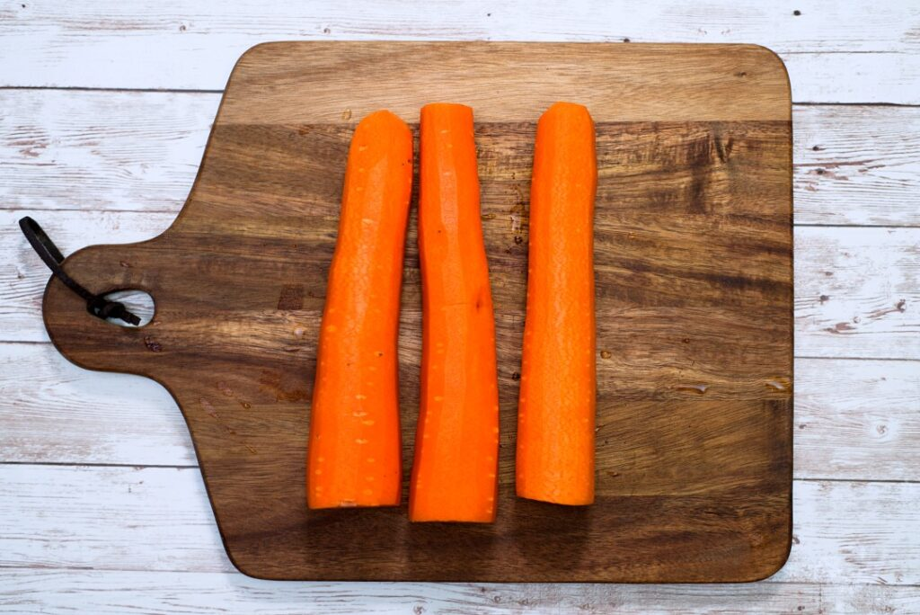 3 peeled carrots on a cutting board.