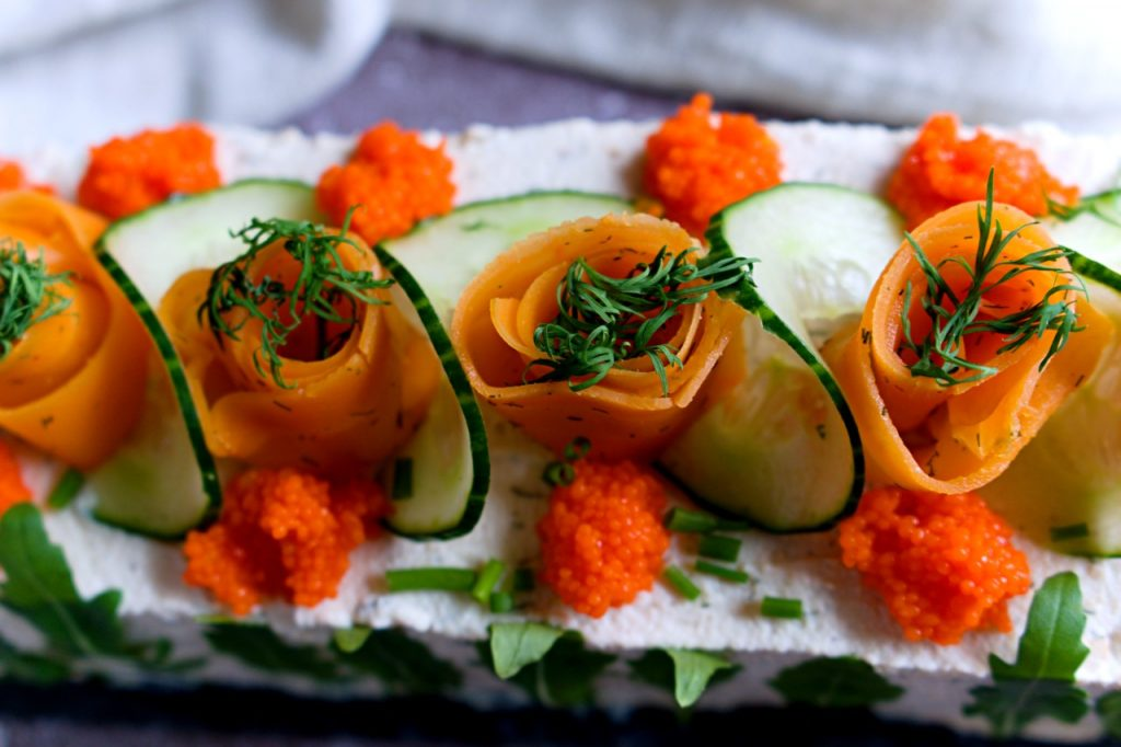 carrot lox roses on top of sandwich cake.