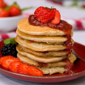 strawberry pancakes in pile with strawberry jam and strawberries.